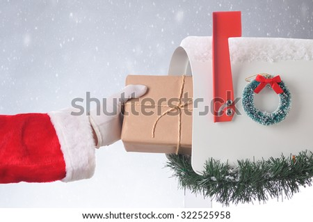 Santa Claus putting a plain brown paper wrapped package in a mailbox. Horizontal format with a snowy background. - stock photo
