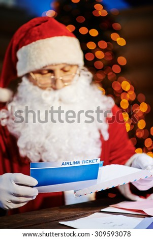 Santa Claus putting airline tickets into envelope - stock photo