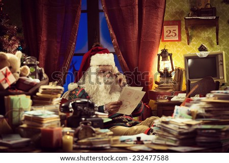 Santa Claus reading a Christmas letter sitting at his messy desk at home - stock photo