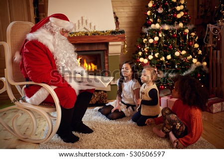 Santa Claus reading fairy tale with little children