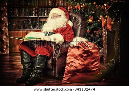Santa Claus reading letters from children and looking at the world map. He is at home, decorated for Christmas. Santa's mail. - stock photo