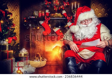 Santa Claus reading letters from children. He is at home, decorated for Christmas. Santa's mail.  - stock photo
