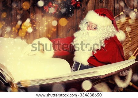 Santa Claus reading magic book in his wooden house. The magic of Christmas. - stock photo
