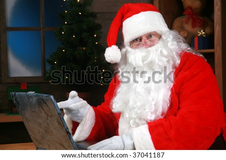 Santa Claus reads and responds to his e-mail while on his laptop computer over the internet - stock photo