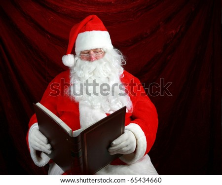 """Santa Claus reads from his book his notes on all the """"Naughty or Nice"""" children from around the world so he knows who to give a nice present to and who to leave a """"Lump of coal"""" in their stocking - stock photo"""