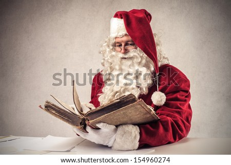 Santa Claus reads old book - stock photo
