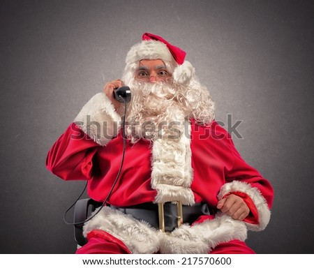 Santa Claus receives requests of prestens via telephone - stock photo