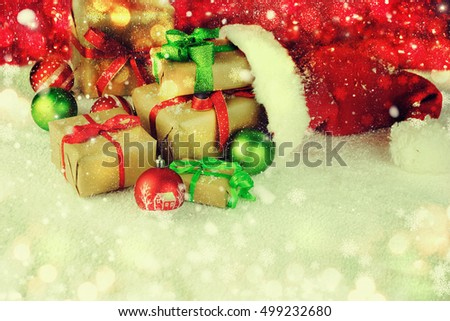 Santa Claus red hat with Christmas balls and gift box on snow.