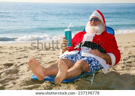 Santa Claus relaxes lying on the beach on some tropical island in the sun. Santa Claus enjoys a well earned vacation after delivering Christmas presents to good boys and girls. Santa loves the beach - stock photo