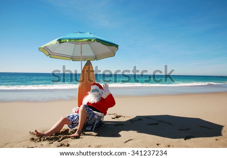 Santa Claus relaxes on his Lounge Chair with his Surf Board, under his beach umbrella at the beach with the beautiful blue ocean in the background. Focus on Santa's Face. Santa Vacation.  - stock photo