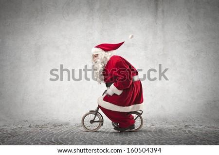Santa Claus rides a bicycle - stock photo