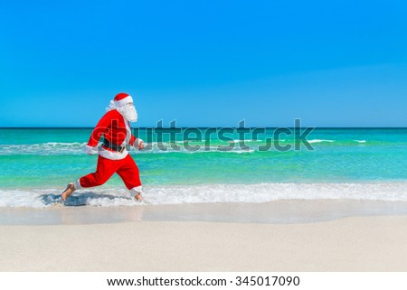 Santa Claus running at sandy tropical sea beach on waves foam splashes, Christmas and New Year's vacation in hot countries concept - stock photo