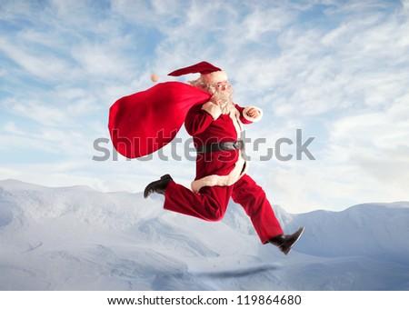 Santa Claus running in the sky - stock photo