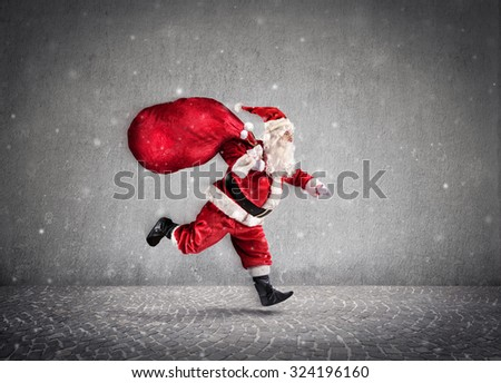 Santa Claus Running With A bag Of Gifts On Way - Wall Background  - stock photo