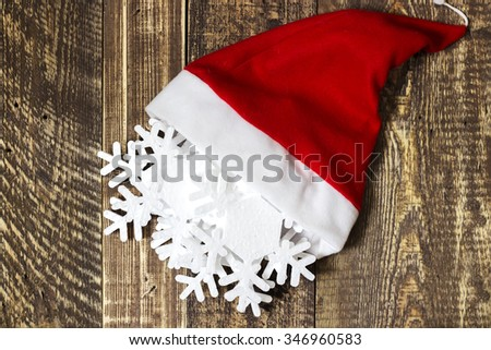 Santa Claus's cap and Christmas decorations on wooden texture