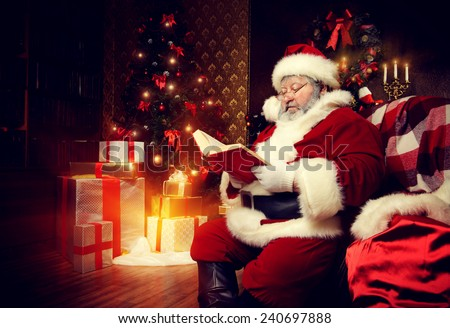 Santa Claus sat down to rest by the fireplace and to read a book. Home decoration. - stock photo