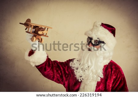 Santa Claus senior man playing with vintage wooden airplane against grunge background. Xmas holiday and winter vacation concept - stock photo