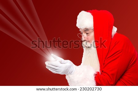 Santa claus showing magical lights in hands - stock photo