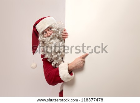 Santa Claus showing something on a white wall - stock photo
