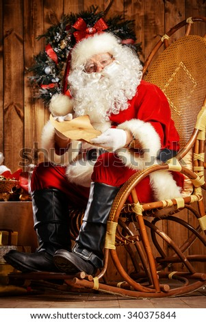 Santa Claus sitting at his wooden house in a comfortable chair and reading a letter.  - stock photo