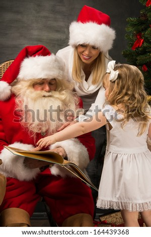 Santa Claus sitting at home with family - little girl and her mother and reading book all together - stock photo