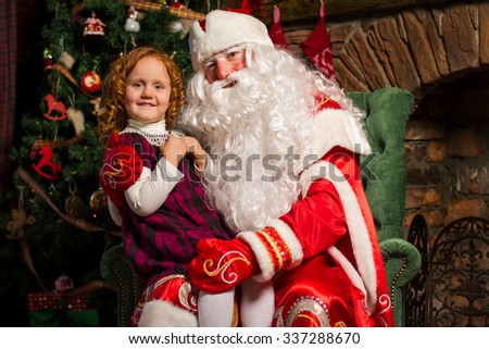 Santa Claus sitting in a chair with a little girl. Fireplace and Christmas tree in the background