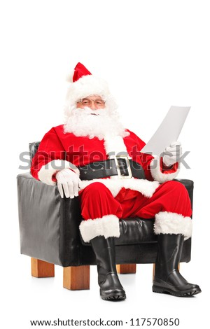 Santa Claus sitting in a comfortable armchair and reading a letter isolated on white background - stock photo