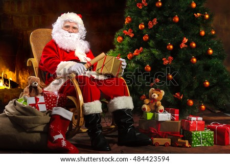 Santa Claus sitting in front of fireplace near Christmas tree with a bag full of presents and a wish list