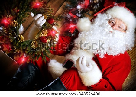 Santa Claus sitting in his wooden house in a comfortable chair and prepare gifts for Christmas. He is holding a Christmas wreath. - stock photo