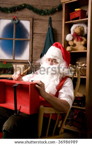 Santa Claus sitting in Rocking Chair in Workshop With Red wooden Wagon on his Lap, Vertical Composition