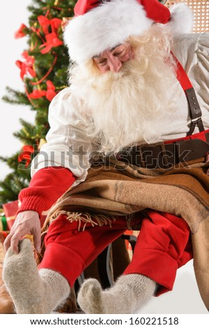 Santa Claus sitting in rocking chair near Christmas Tree at home and massages his foot