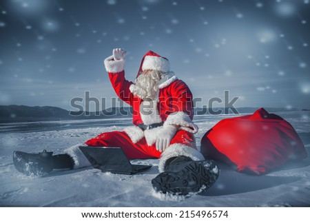 Santa Claus sitting in the snow with a laptop and looking away from the arms - stock photo