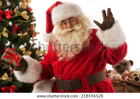 Santa Claus sitting near Christmas tree presenting gift box - stock photo