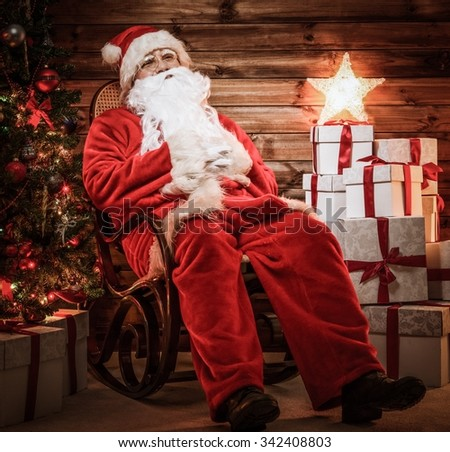 Santa Claus sitting on rocking chair in wooden home interior with illuminated star on gift boxes