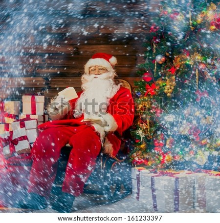Santa Claus sitting on rocking chair in wooden home interior with letters in hands