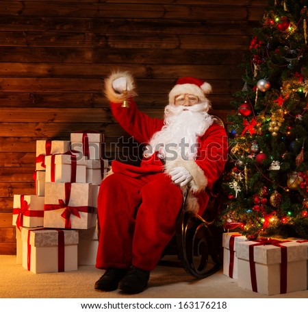 Santa Claus sitting on rocking chair in wooden home interior with little bell in his hand