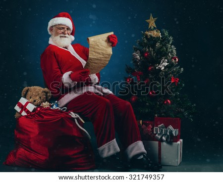 Santa Claus sitting on the pile of Christmas presents and reading wish list