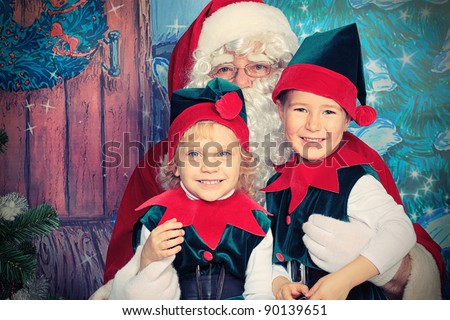 Santa Claus sitting with two little cute elves over Christmas background. - stock photo