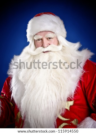 Santa Claus smiling on blue background - stock photo