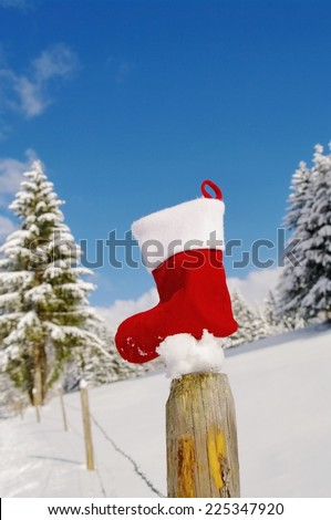 Santa Claus sock outside in winter landscape - stock photo