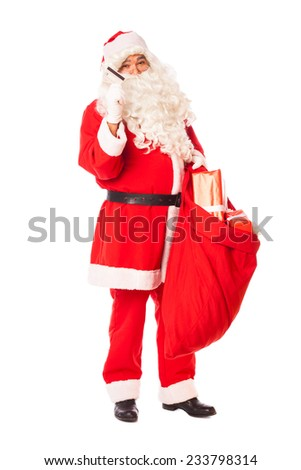 santa claus standing and holding a credit card and sack of gifts in hands, isolated - stock photo