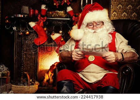 Santa Claus standing at home with gifts, dressed in his home clothes. Christmas. Decoration. - stock photo