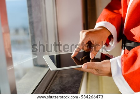 Santa Claus standing at window and using apps resize on a touch screen tablet, Christmas and technology concept