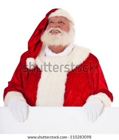 Santa Claus standing behind blank sign looking up. All on white background. - stock photo