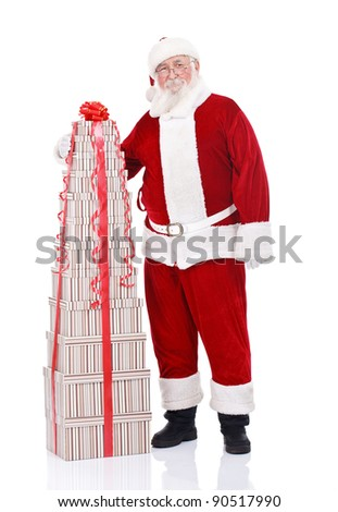 Santa Claus standing beside large stack of gift boxes, isolated on white background - stock photo