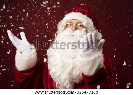 Santa Claus standing in the snowy scenery  - stock photo