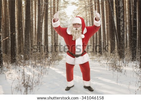Santa Claus standing in winter forest and thumbs up - stock photo