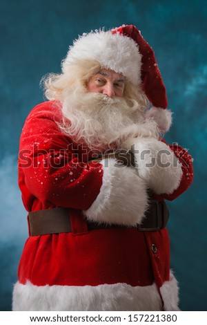 Santa Claus standing outdoors at snowfall at north pole with hands folded - stock photo