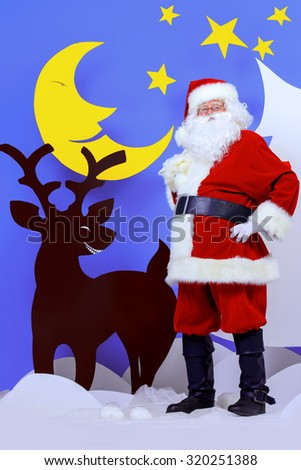 Santa Claus standing with a reindeer in a cartoon fairy snowy forest. Full length portrait. - stock photo