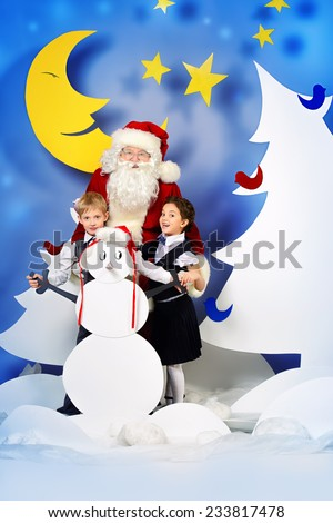 Santa Claus standing with happy children in a cartoon fairy snowy forest. Full length portrait. - stock photo
